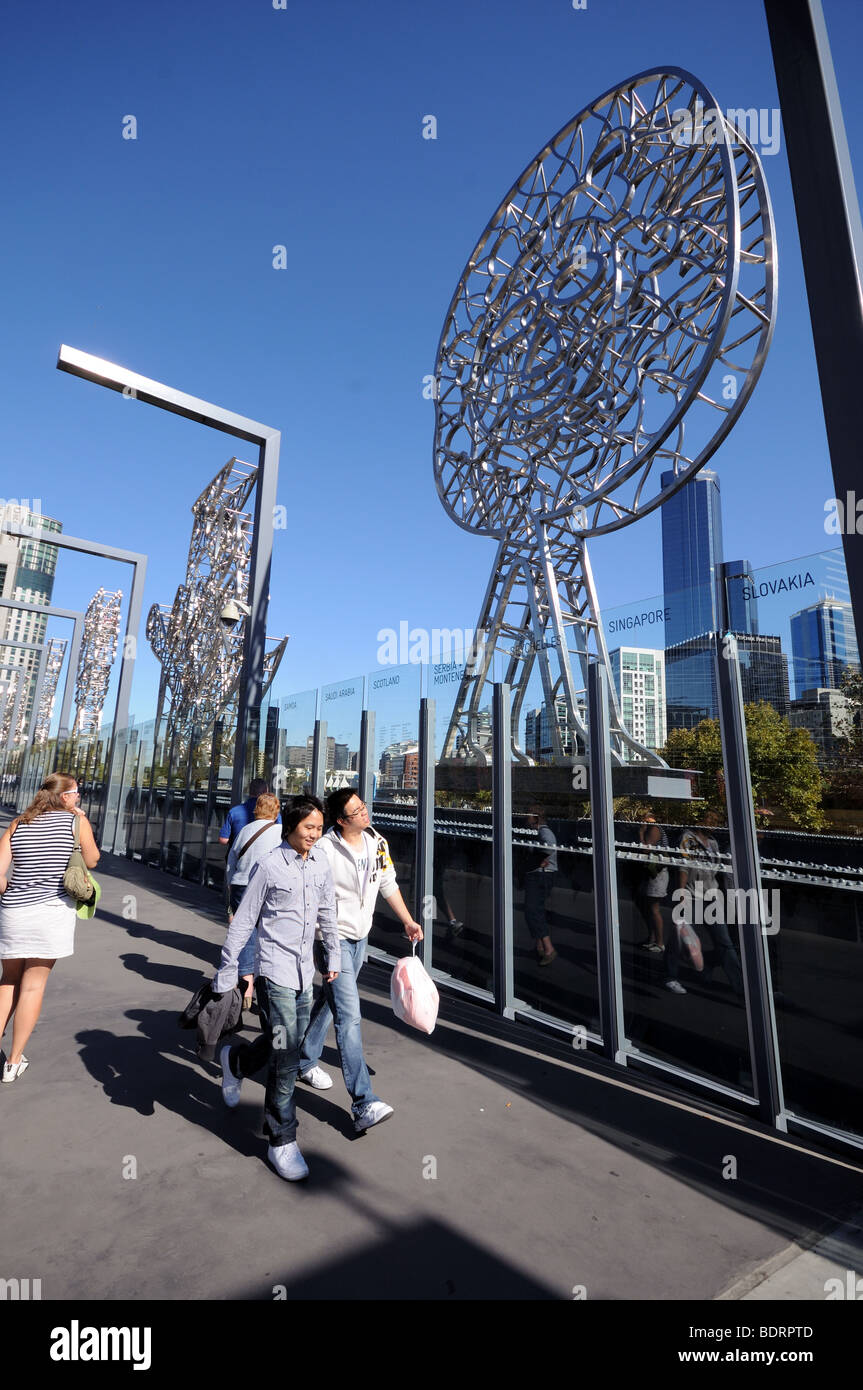 Young asian tourists walk past symbolic metal art work Sandridge Immigration Bridge Yarra River Melbourne Australia - Stock Image