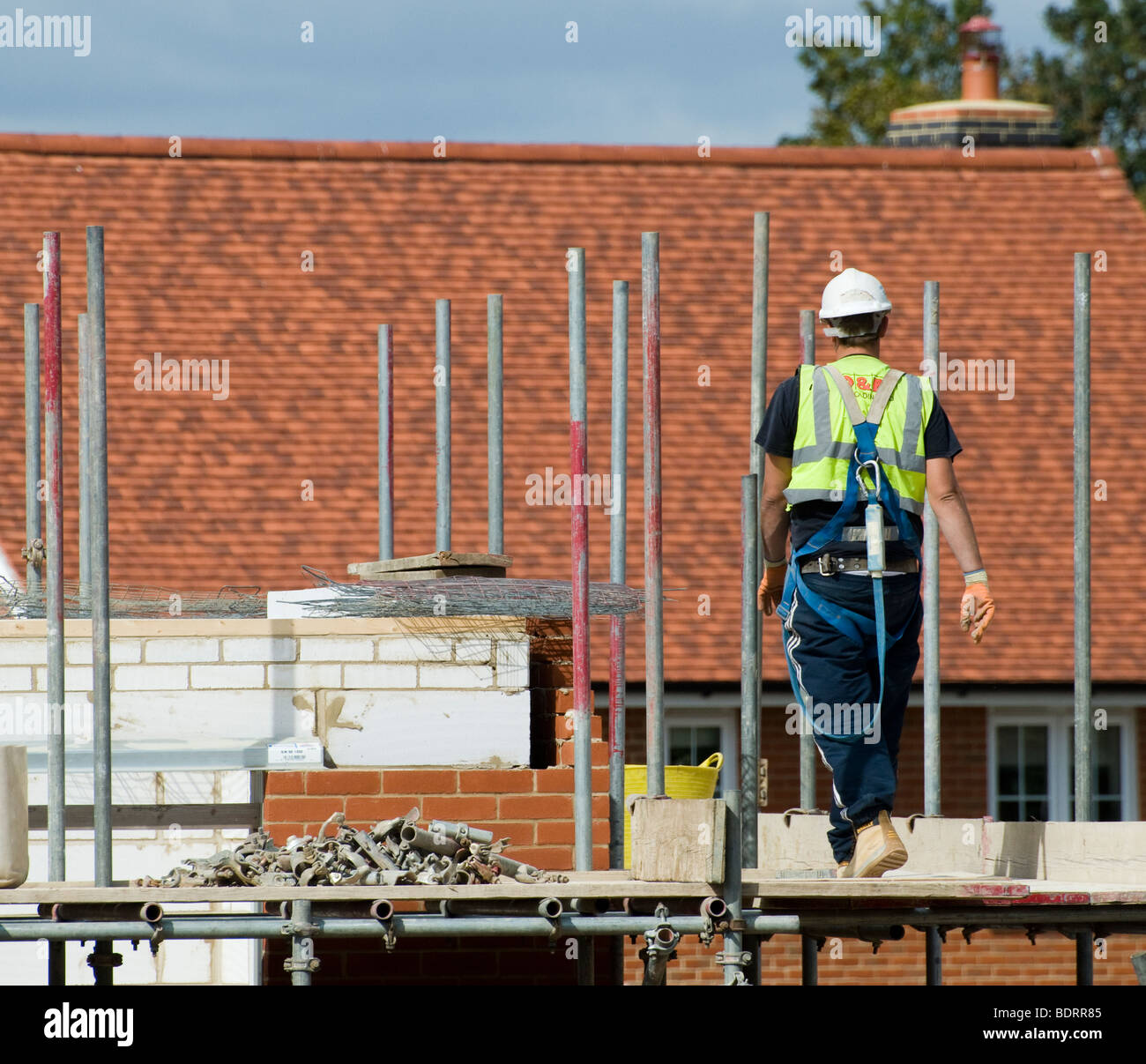 Construction site worker walking across scaffolding platform. - Stock Image