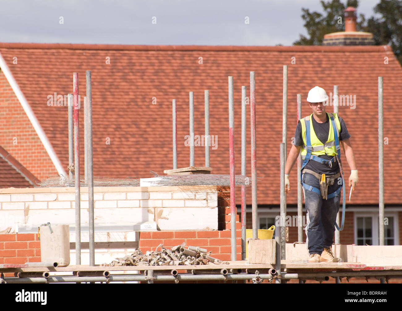 A Construction worker walking across scaffolding platform by a house under construction. - Stock Image