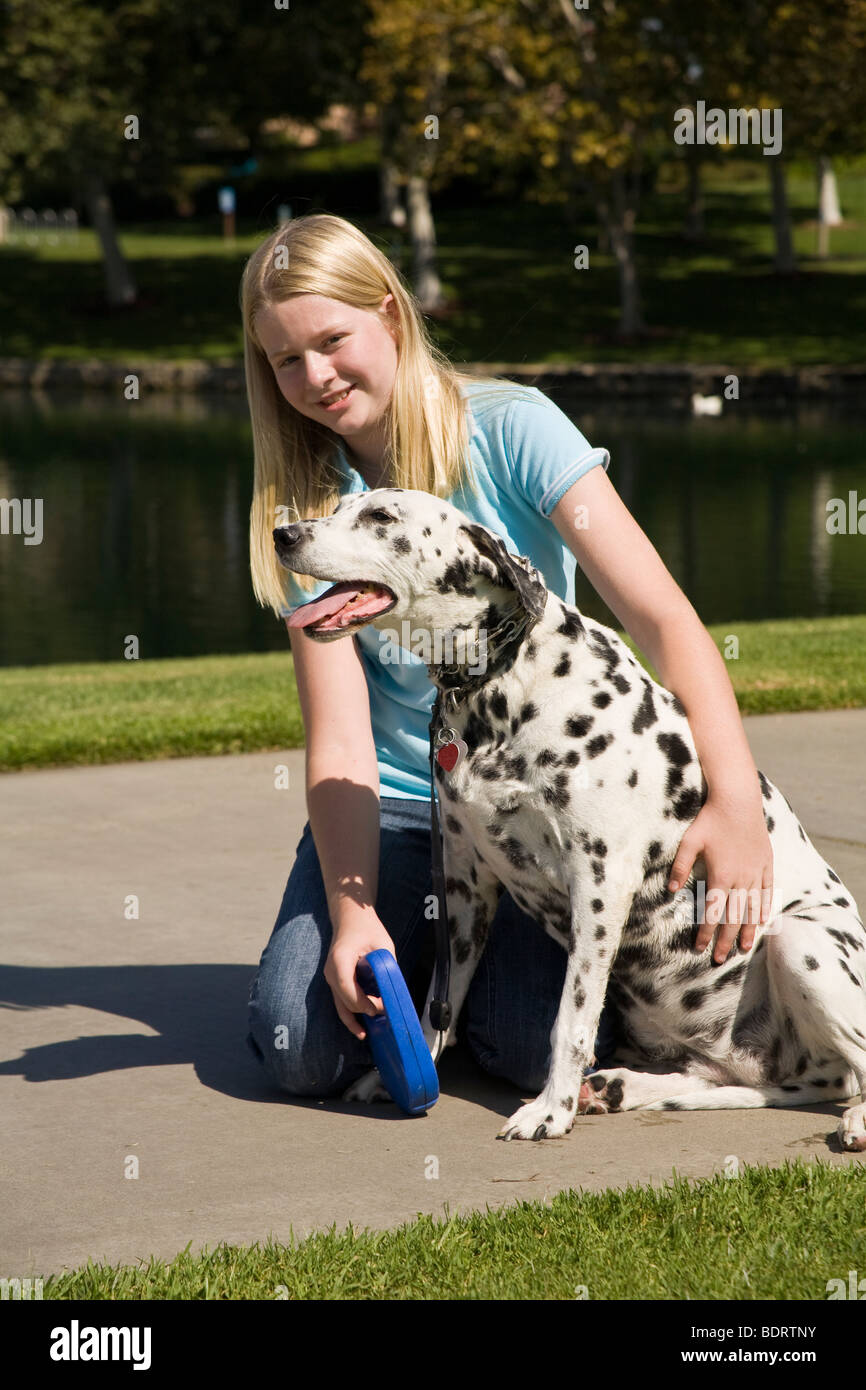 Caucasian girl 11-13 year years old resting her dalmatian dog during walk owner child playing play plays dog profile - Stock Image