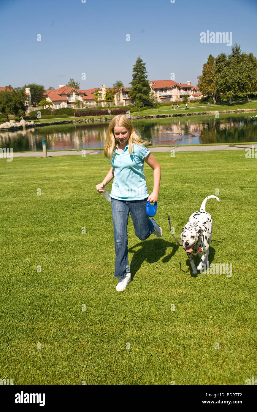 Caucasian junior high age girl 11-13 year old years child playing play plays dog dalmatian dog owner front view - Stock Image