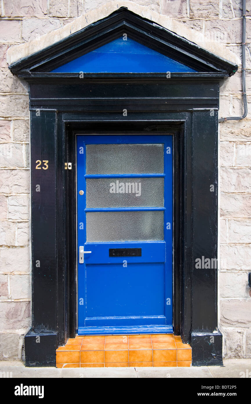 Classic surround with pediment and modern glazed front door No 23 with tiled step UK - Stock Image
