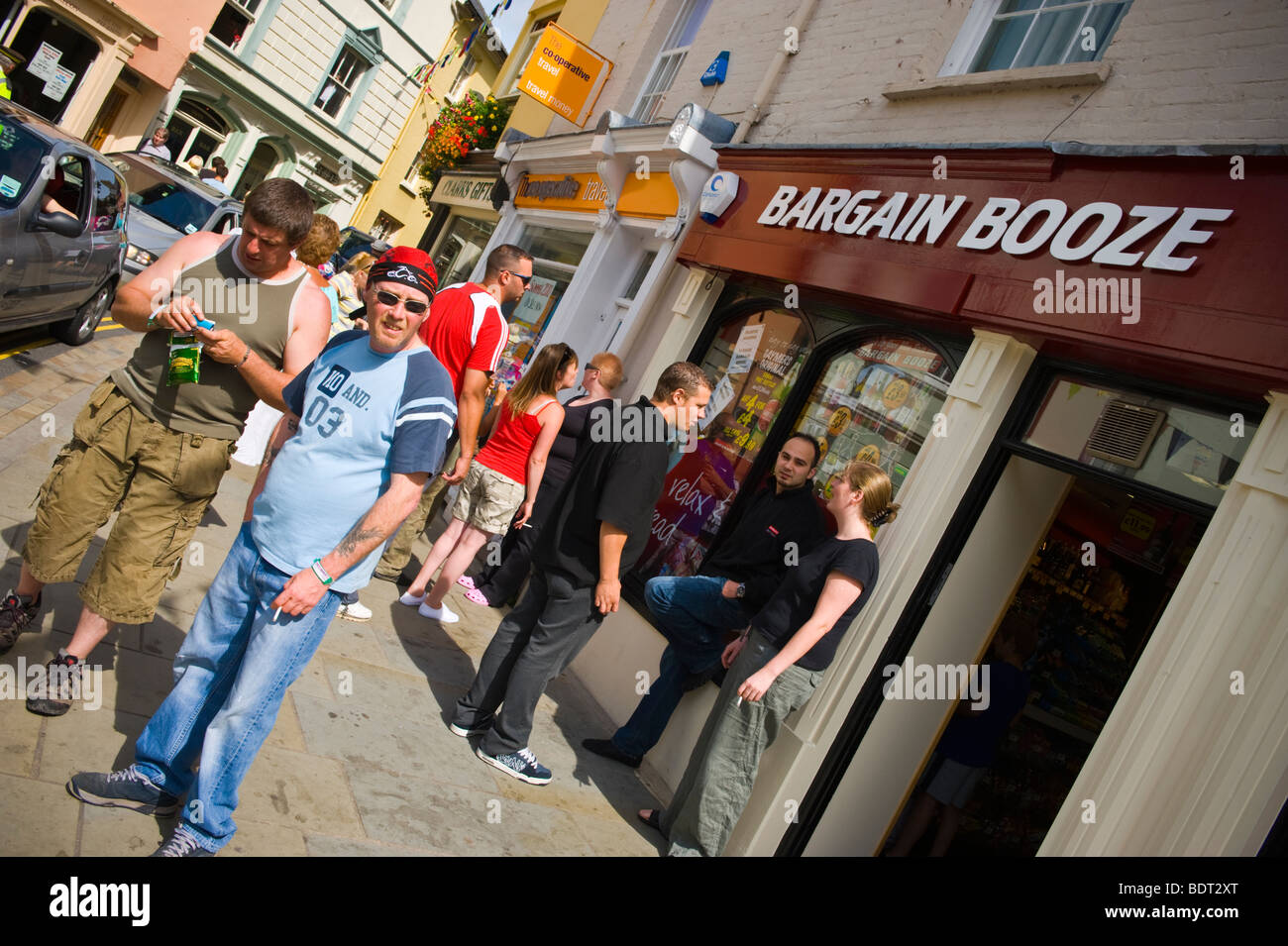 Visitors to Brecon Jazz Festival 2009 standing around outside outside the Bargain Booze shop - Stock Image