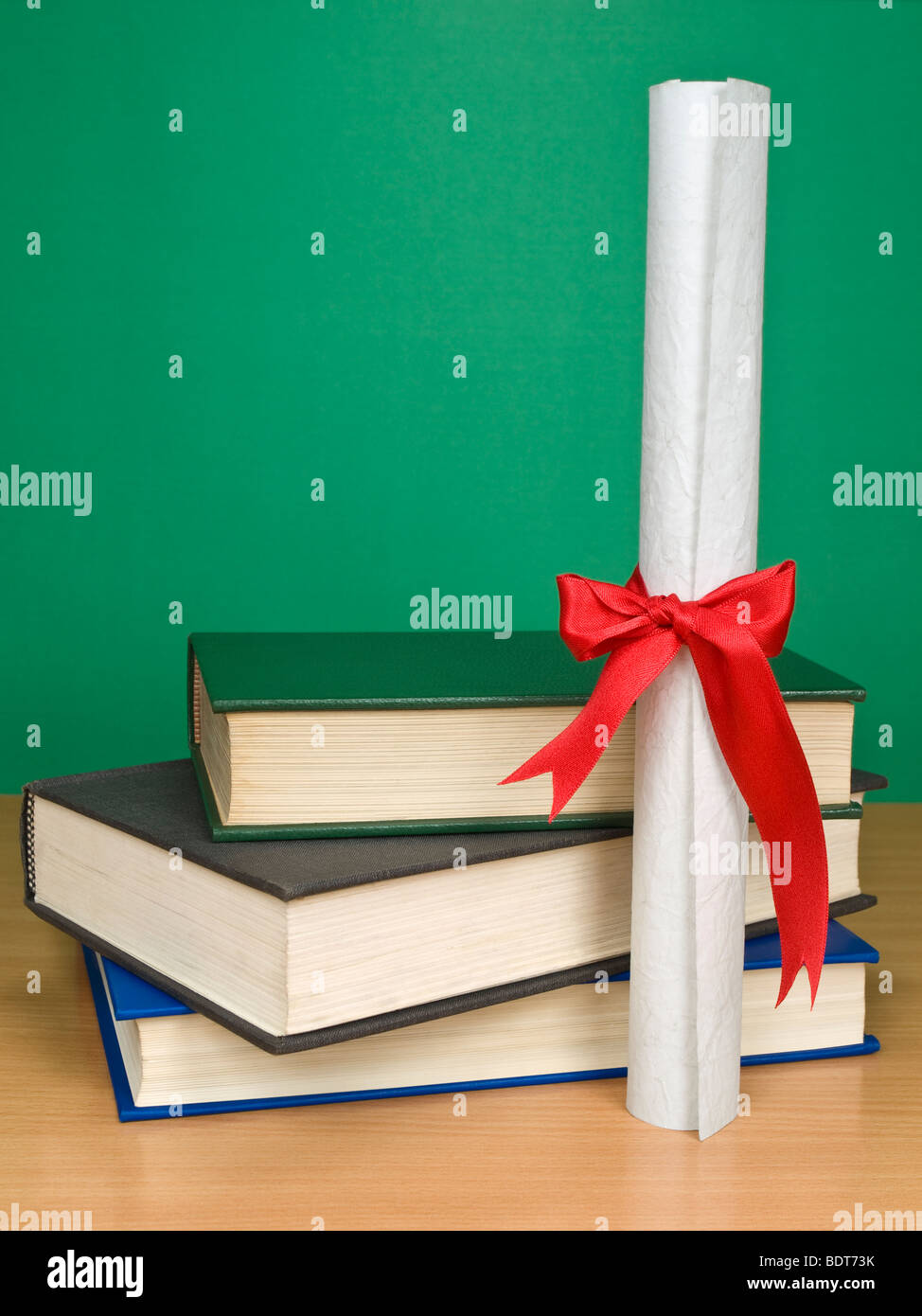 A pile of books and a diploma. Blank chalkboard on the background. - Stock Image