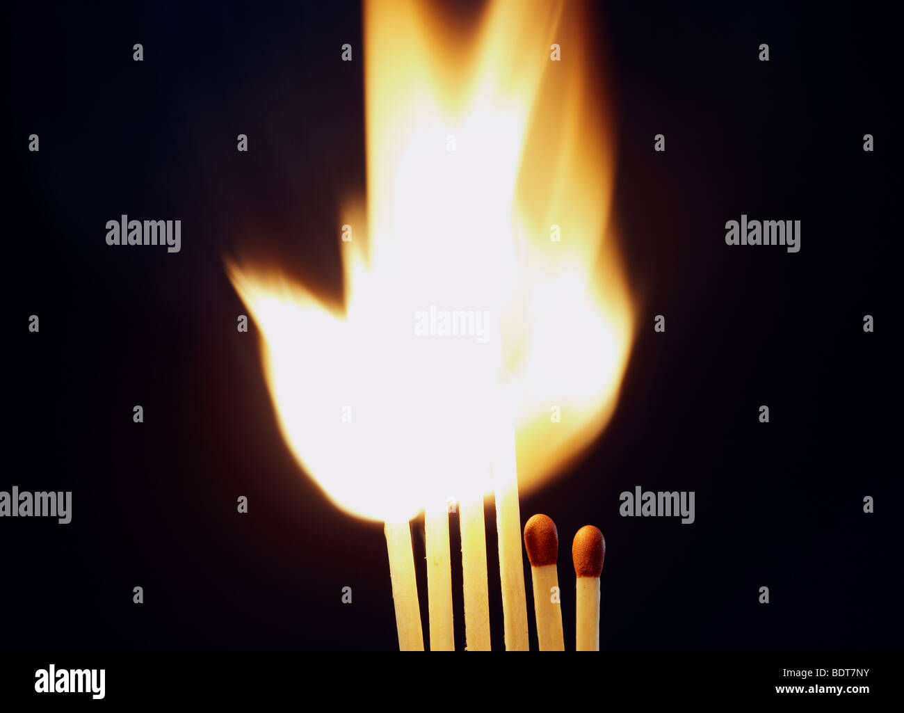 bright flame as four matches are set on fire whilst two shorter ones stay unlit - Stock Image