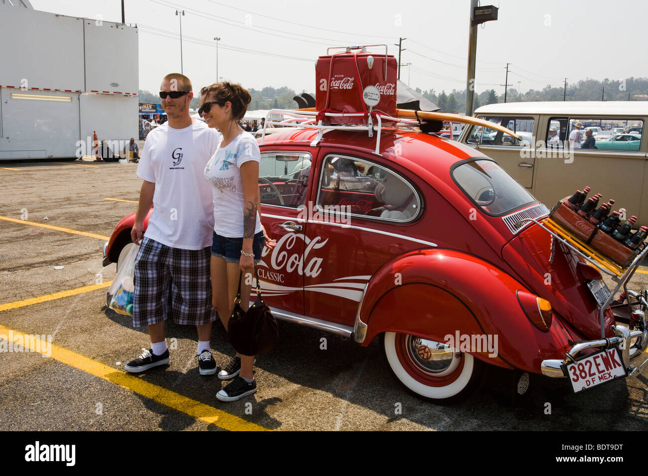 Posing for a picture in front of a classic VW Beetle, Pomona Swap Meet - Stock Image