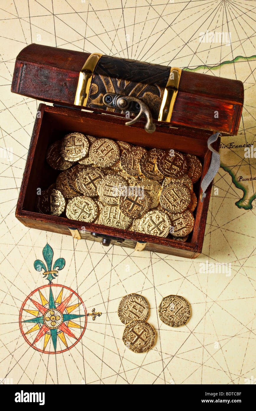 Open treasure chest box on old map with compass rose - Stock Image