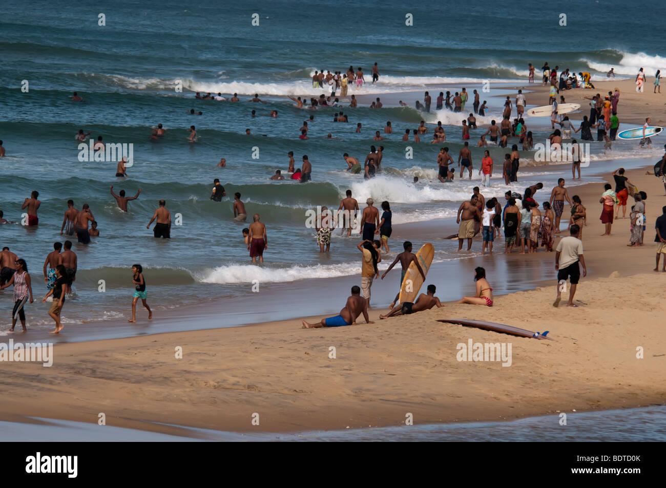Arugam Bay  Sri Lanka busy beach local Asian Indian ocean sand sea people east coast surfers surfing surf - Stock Image
