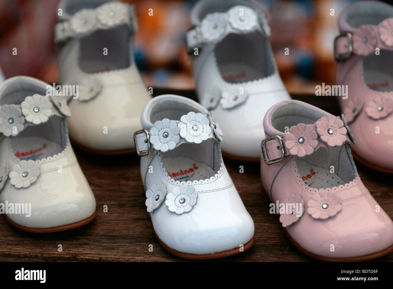 Children's shoes on display at a market - Stock Image