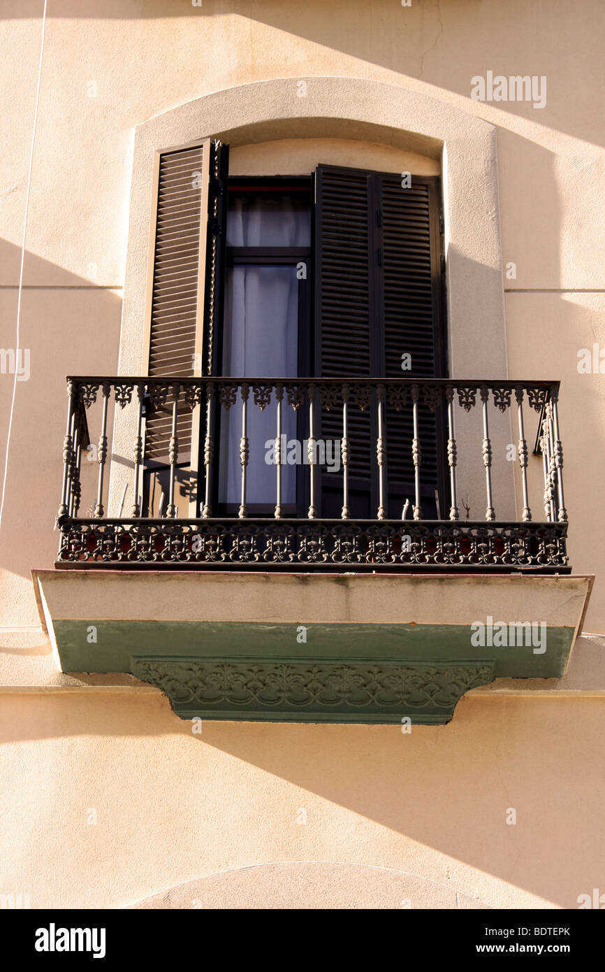 Spanish window with wrought iron balcony and wooden shutters - Stock Image