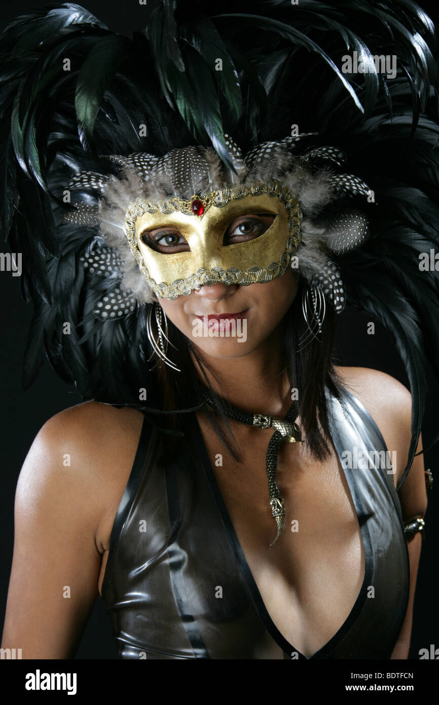 Portrait Of A Sexy Indian Girl Wearing A Black Latex Catsuit And A Feather Carnival Mask