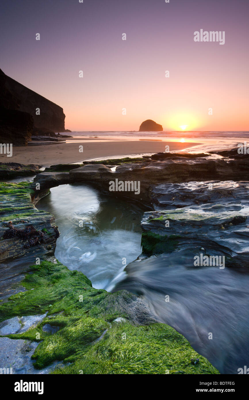 Water channel flowing beneath natural rock arch at Trebarwith Strand beach in Cornwall, England. Spring (April) - Stock Image
