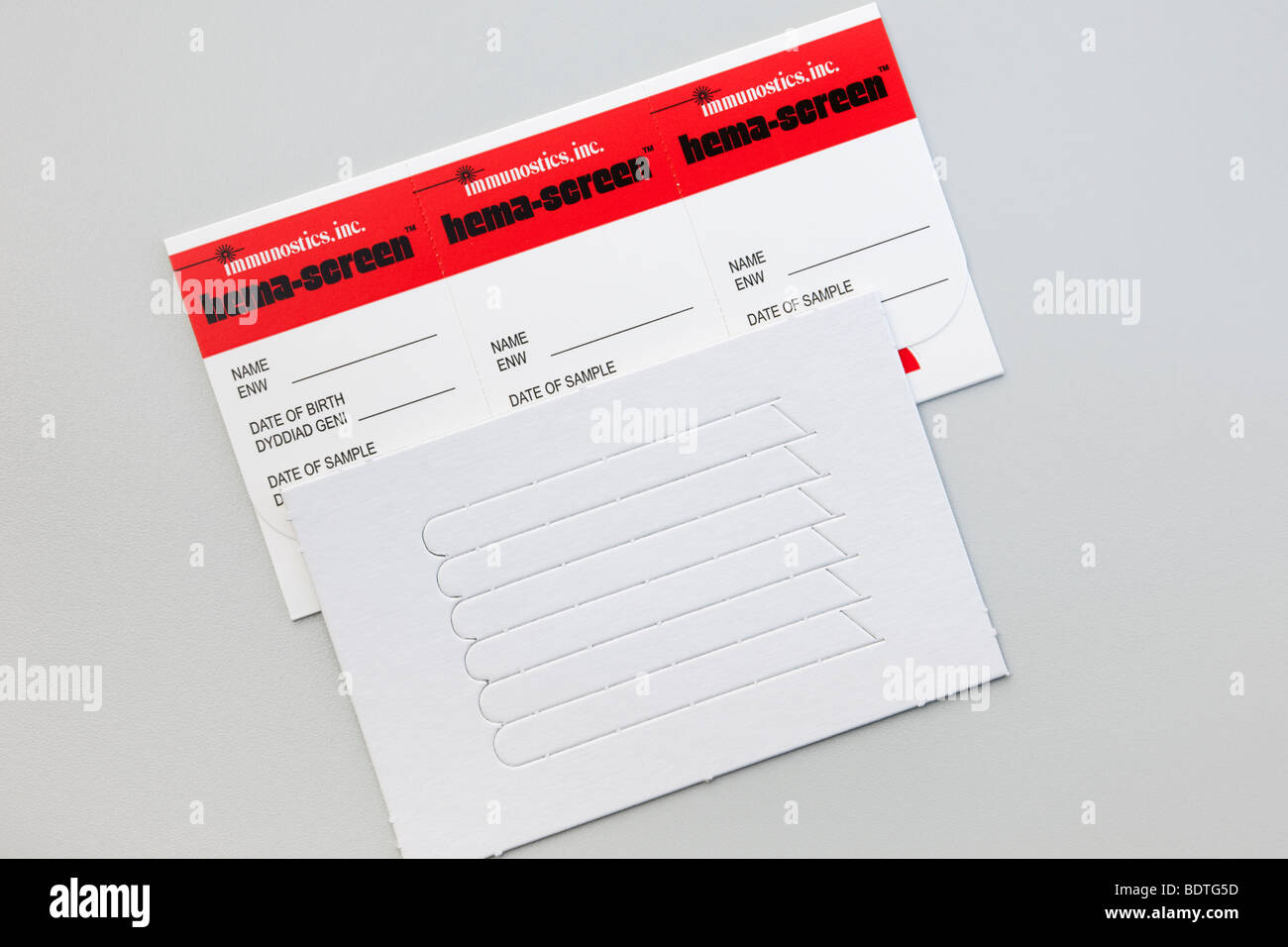 Studio still life UK. Bowel cancer screening kit from National Health Service Wales. - Stock Image