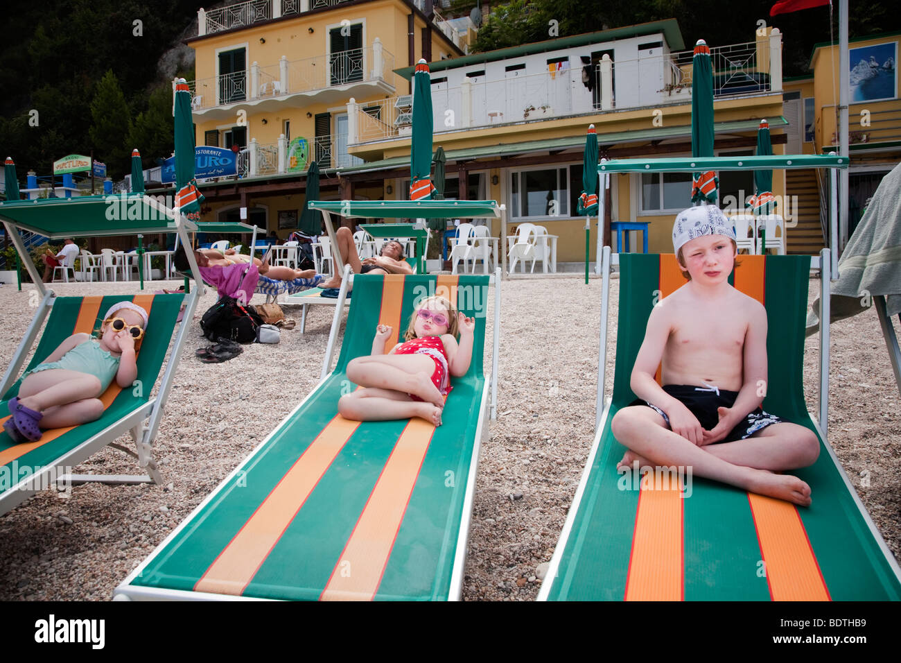 brother and two sisters on stripy beach loungers in italy - Stock Image