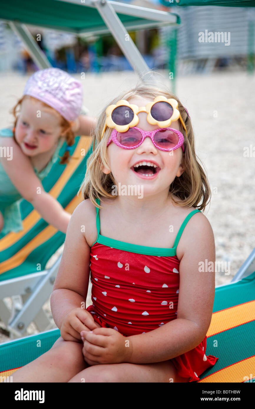 girl on beach wearing two pairs of sunglasses - Stock Image