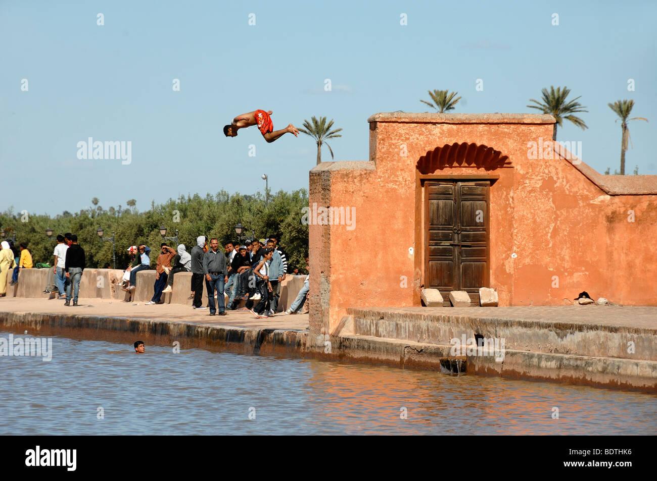 Boys Dive Off the Walls of the Menara Royal Pavilion into the Lake or Pool of the Menara Gardens Marrakesh Morocco - Stock Image