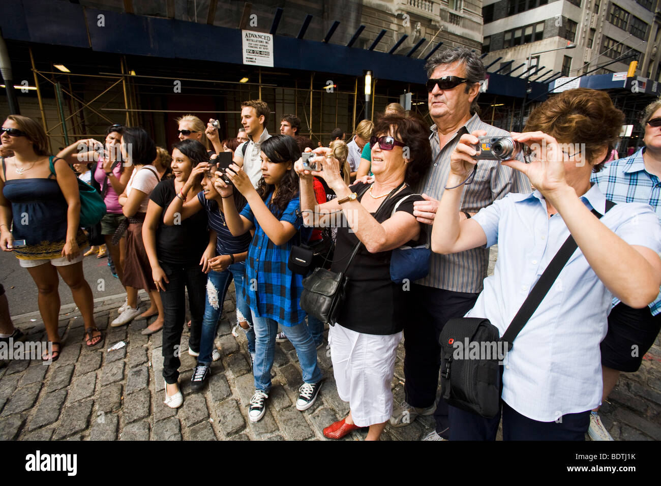 Tourists photographing the Chargin Bull sculpture near 26 Broadway, near Wall Street, Manhattan, New York City, - Stock Image