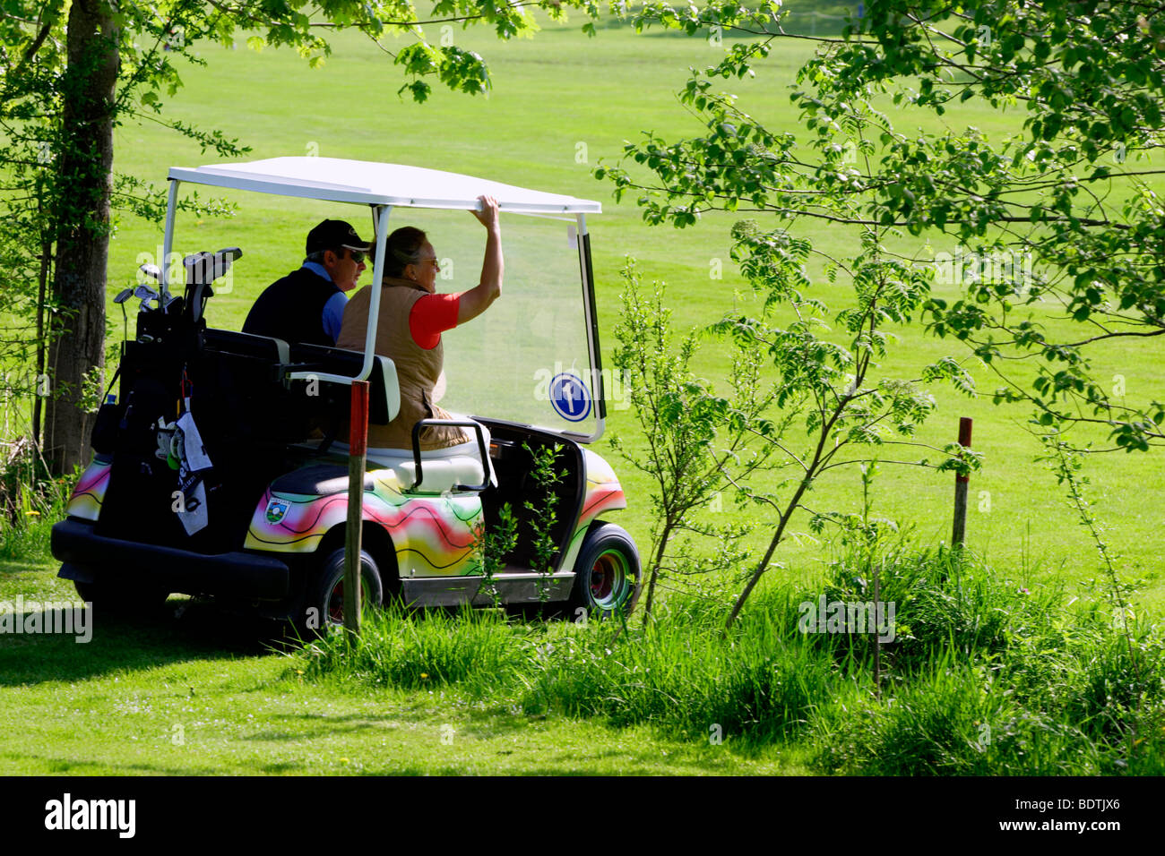 People Riding in a Colourful Golf Buggy on Course - Stock Image