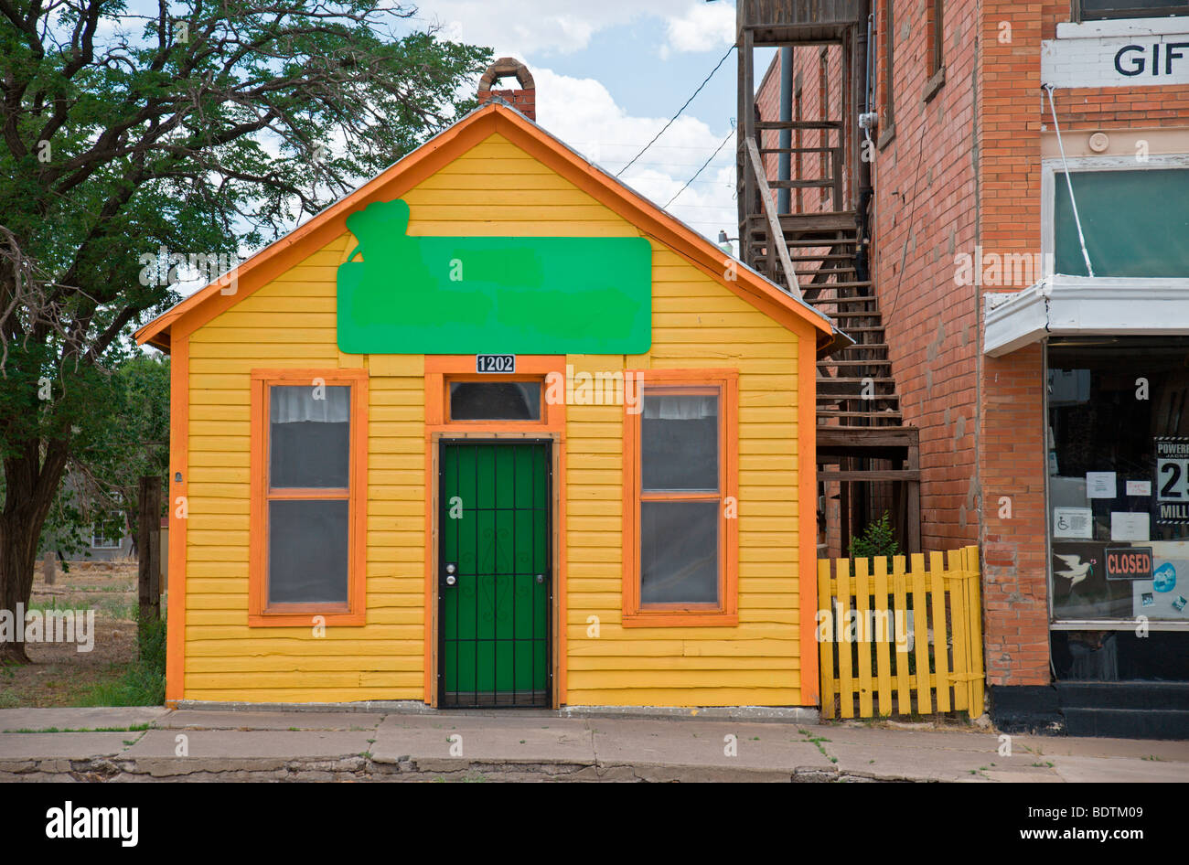 A yellow house with orange trim shines brightly in Carrizozo, New Mexico. - Stock Image