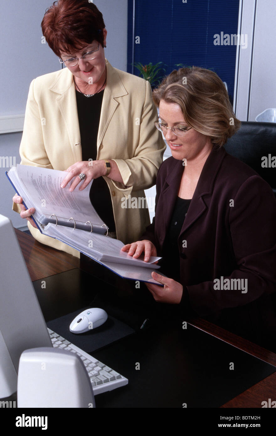 Women in office - woman as boss , female manager talking to older employee - Stock Image
