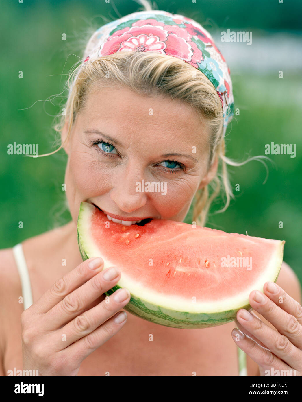 A woman eating a watermelon - Stock Image