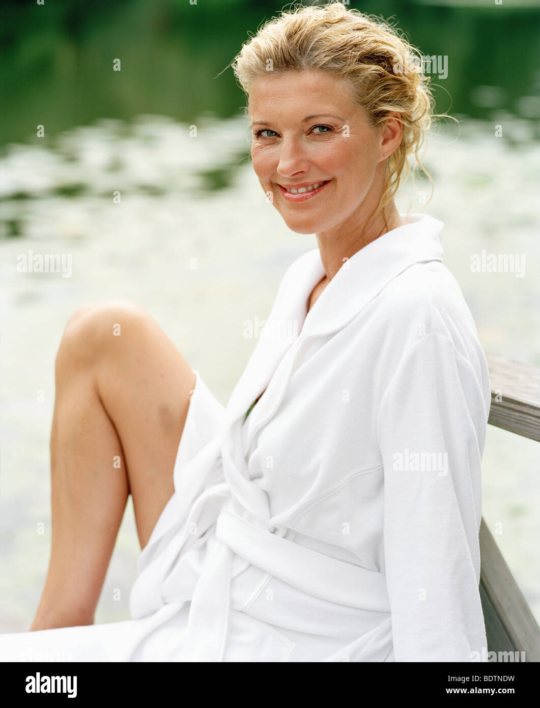 A smiling woman wearing a bathrobe - Stock Image