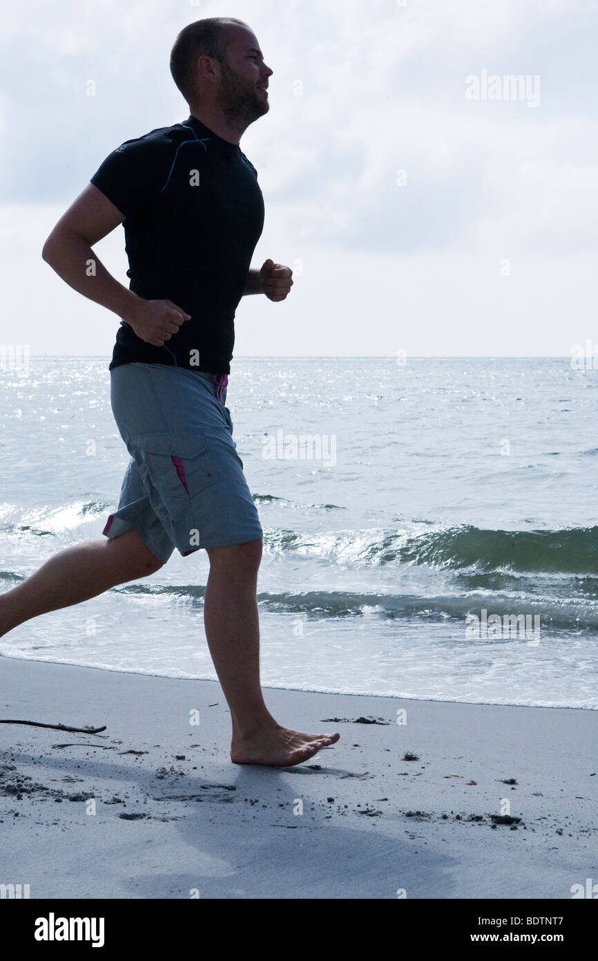 A man jogging by the sea - Stock Image