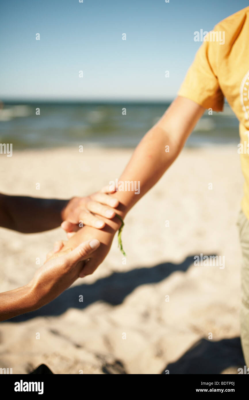 Mother and son using suntan oil Gotland - Stock Image