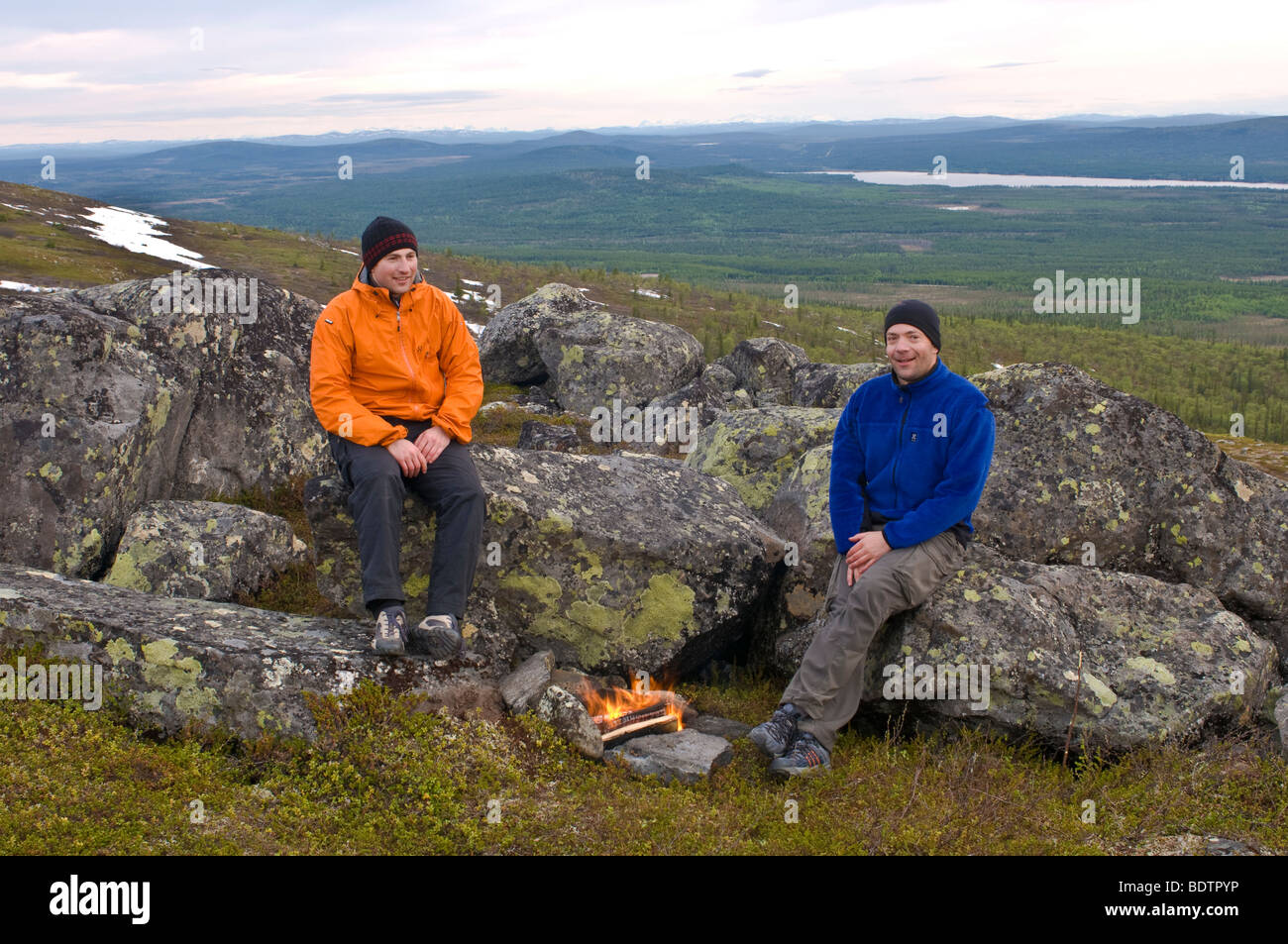 men are grilling at a bon fire in fjell, swedish lapland - Stock Image