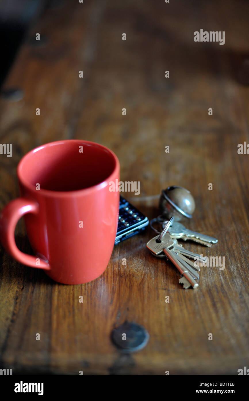 keys and phone next to mug - Stock Image