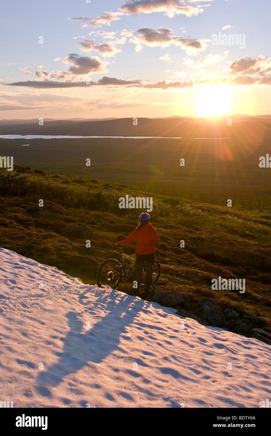 mountainbikerin am rande eines schneefeldes, gaellivare, lappland, schweden, downhill cyclist on a snow field, lapland, Stock Photo
