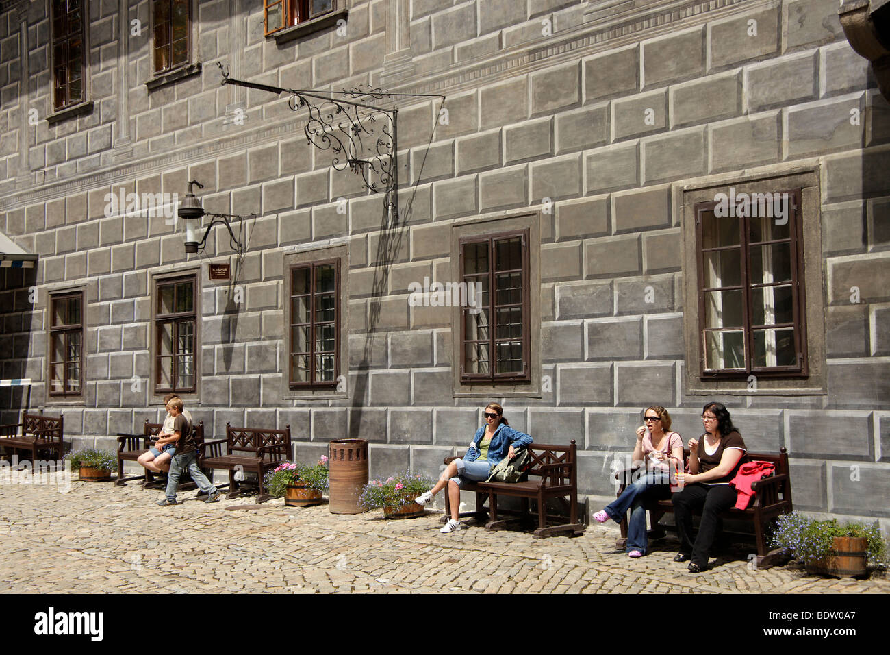visitors sitting in the painted courtyard of the Castle, Cesky Krumlov, Czech Republic, Europe - Stock Image