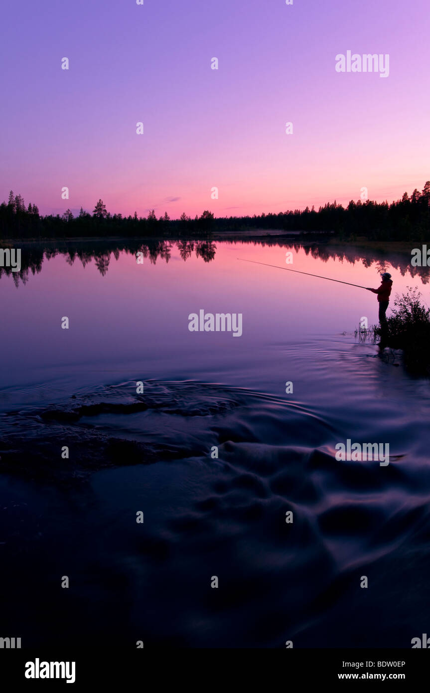 anglerin in abenddaemerung am see in lappland, schweden, female angler at sundwon at lake in swedish lapland - Stock Image