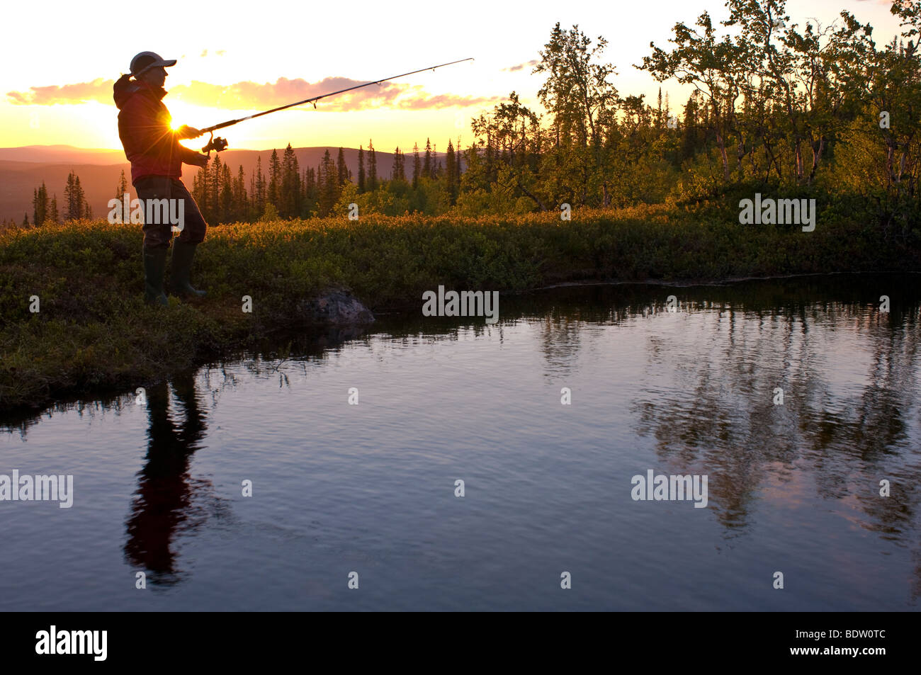 fisher, midnight sun in lapland, sweden Stock Photo