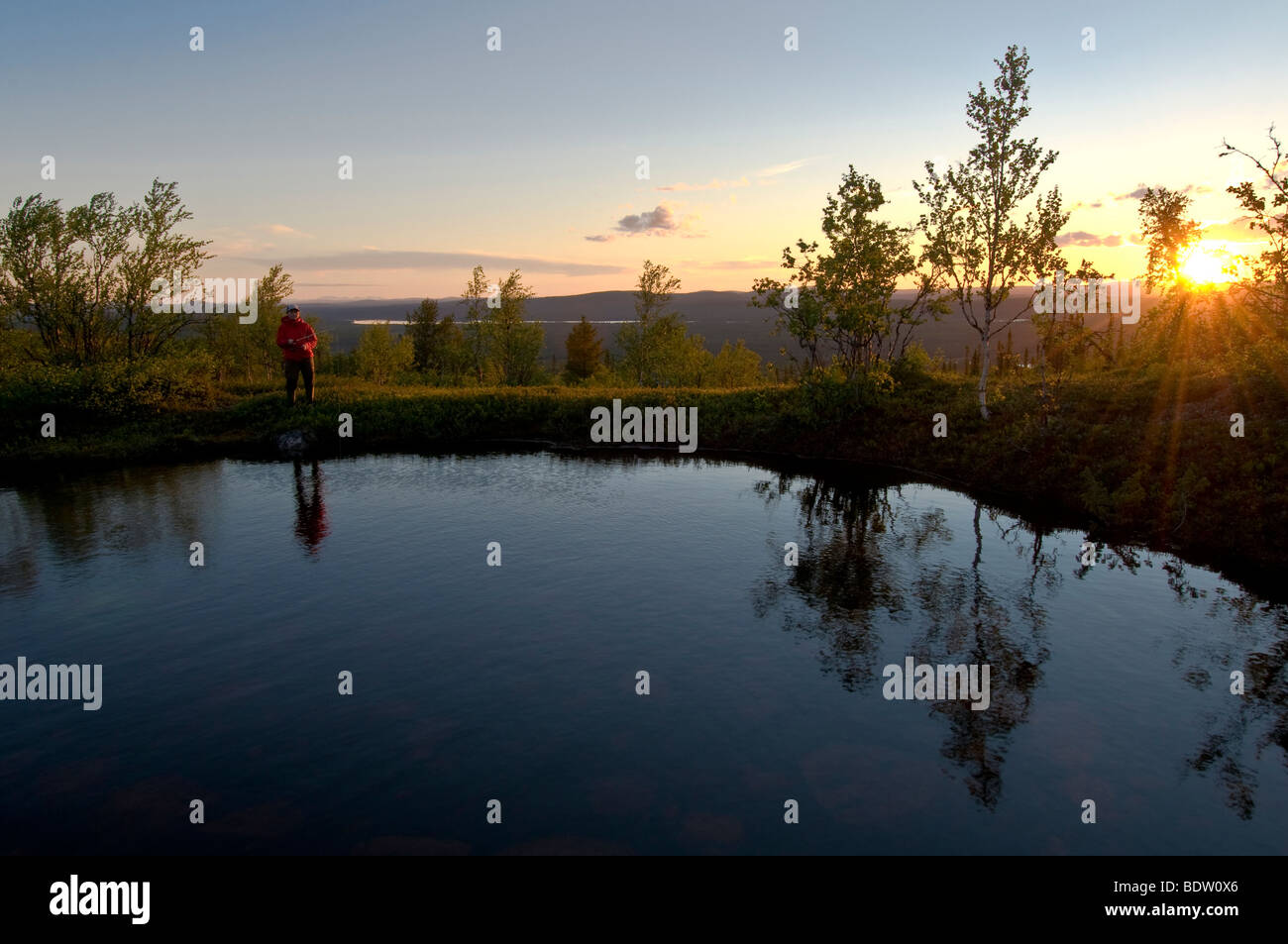 female angler at a mountain lake in lapland at midnight sun, sweden - Stock Image