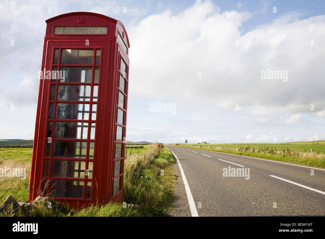 red phone box in scenery, orkney islands, scotland - Stock Image
