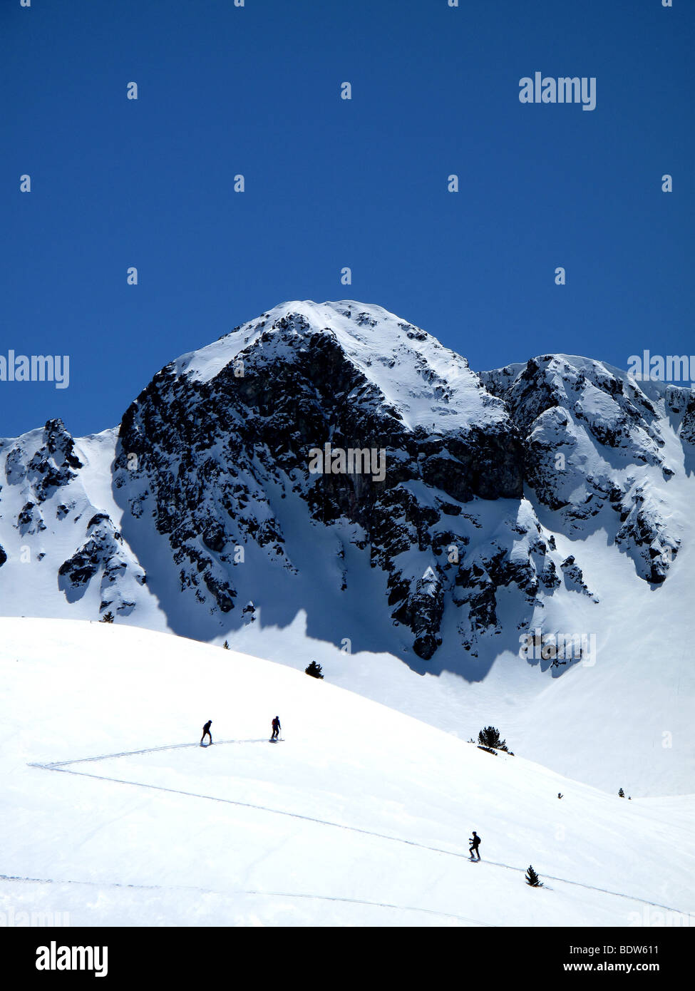 Cross country skiers climb a mountain in andorra - Stock Image