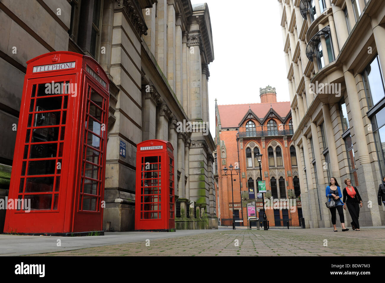 Red phone boxes and Victorian architecture in Eden Place Birmingham England Uk - Stock Image