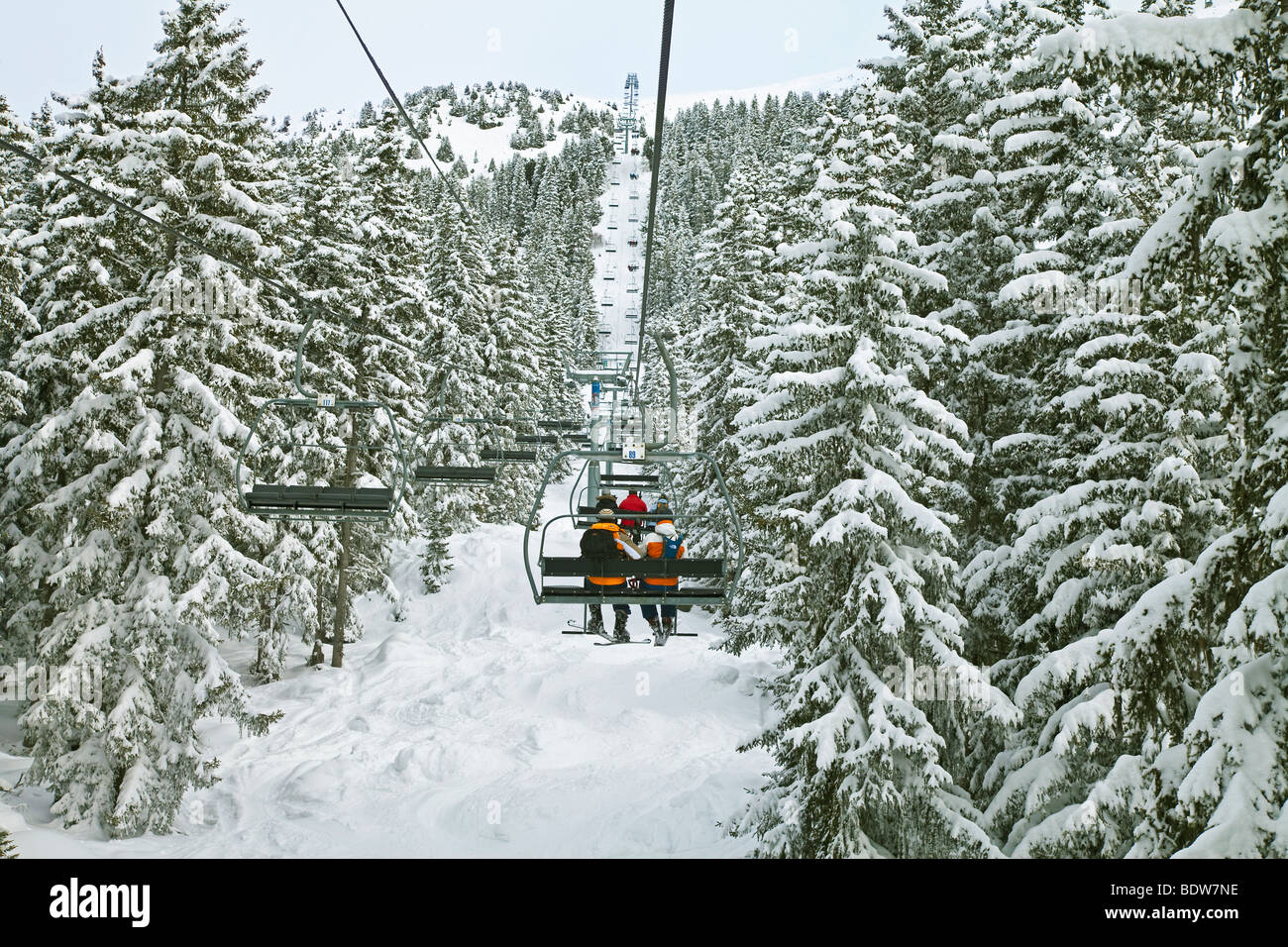 Skiers on a chairlift, Meribel ski resort in the Three Valleys, Les Trois Vallees, Savoie, French Alps, France - Stock Image