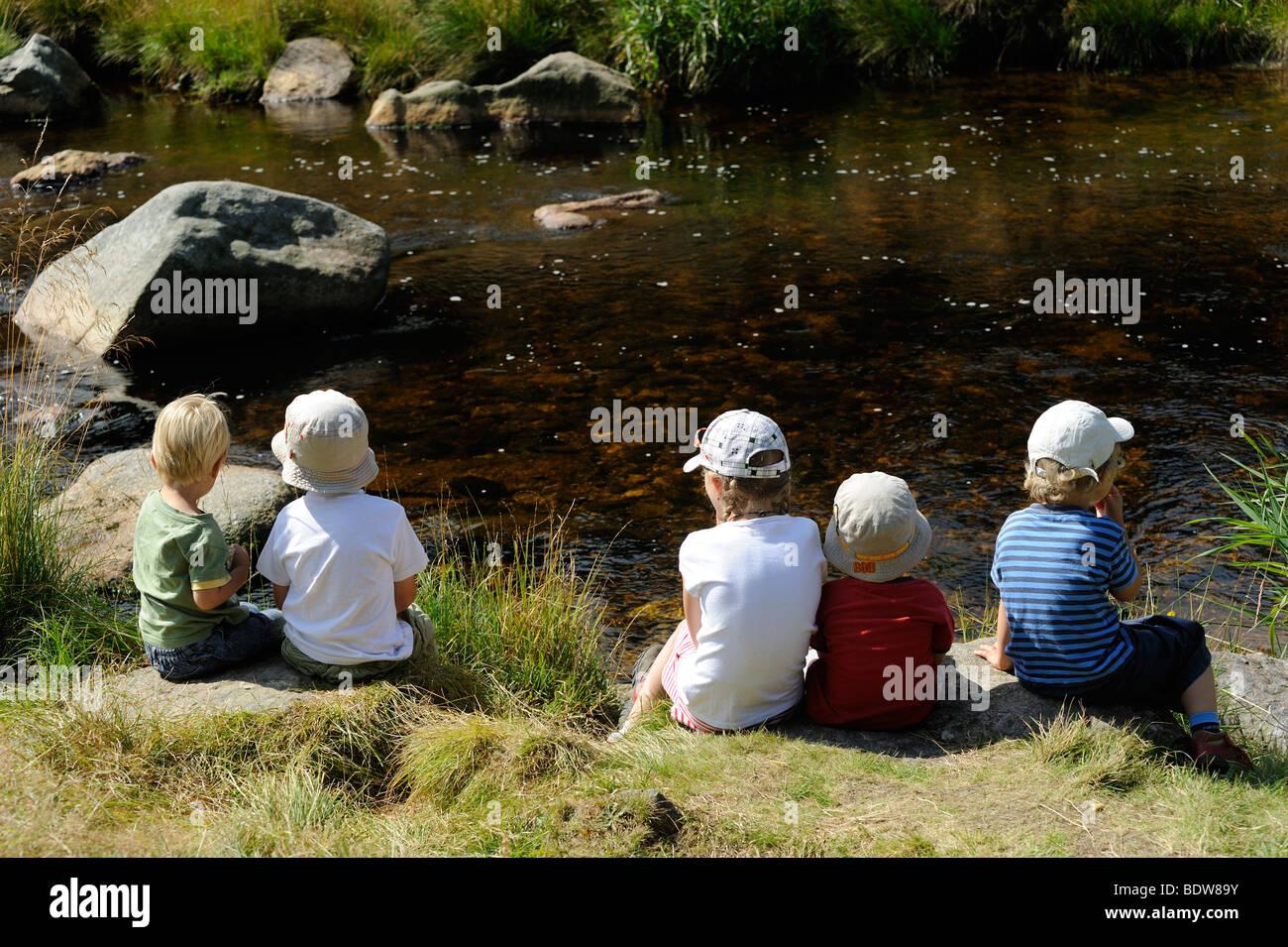 Children sitting on bank of river, Modrava Roklansky potok Sumava National Park Czech Republic - Stock Image