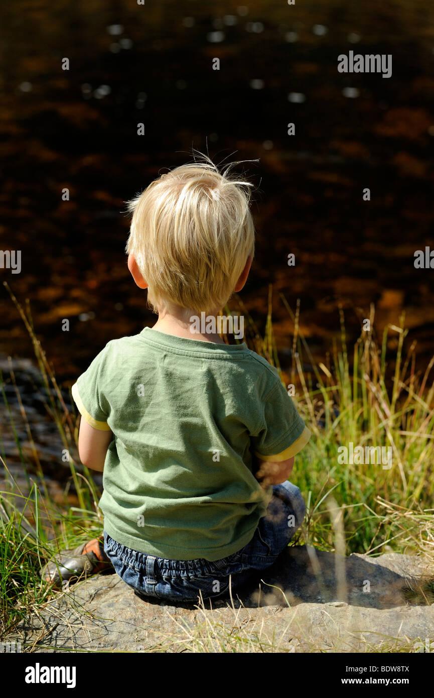 Child sitting on bank of river, Modrava Roklansky potok Sumava National Park Czech Republic - Stock Image
