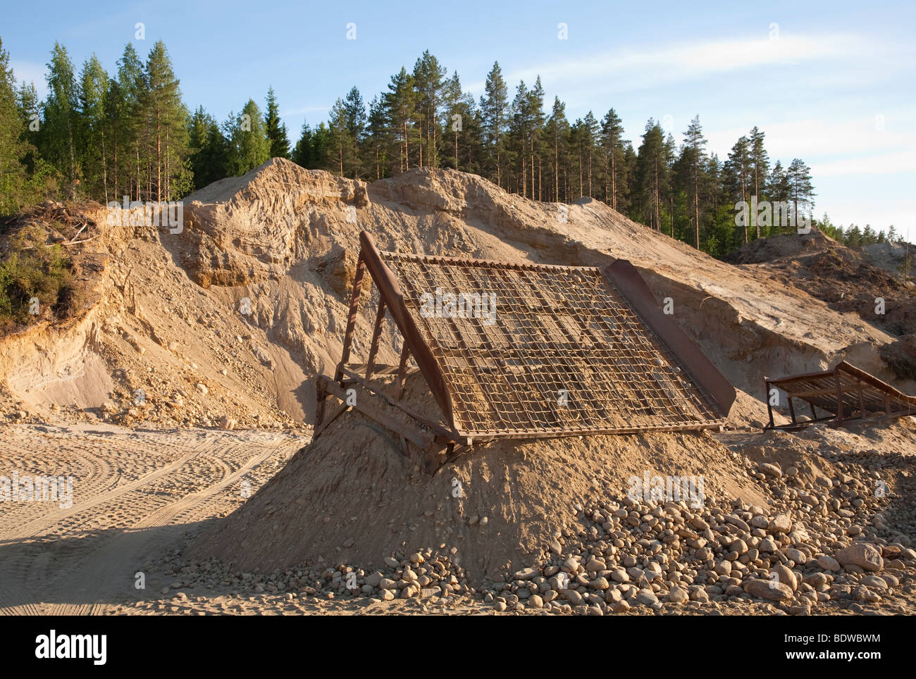 Gravel extraction area with a simple stone sieve for extracting larger stones from sand - Stock Image
