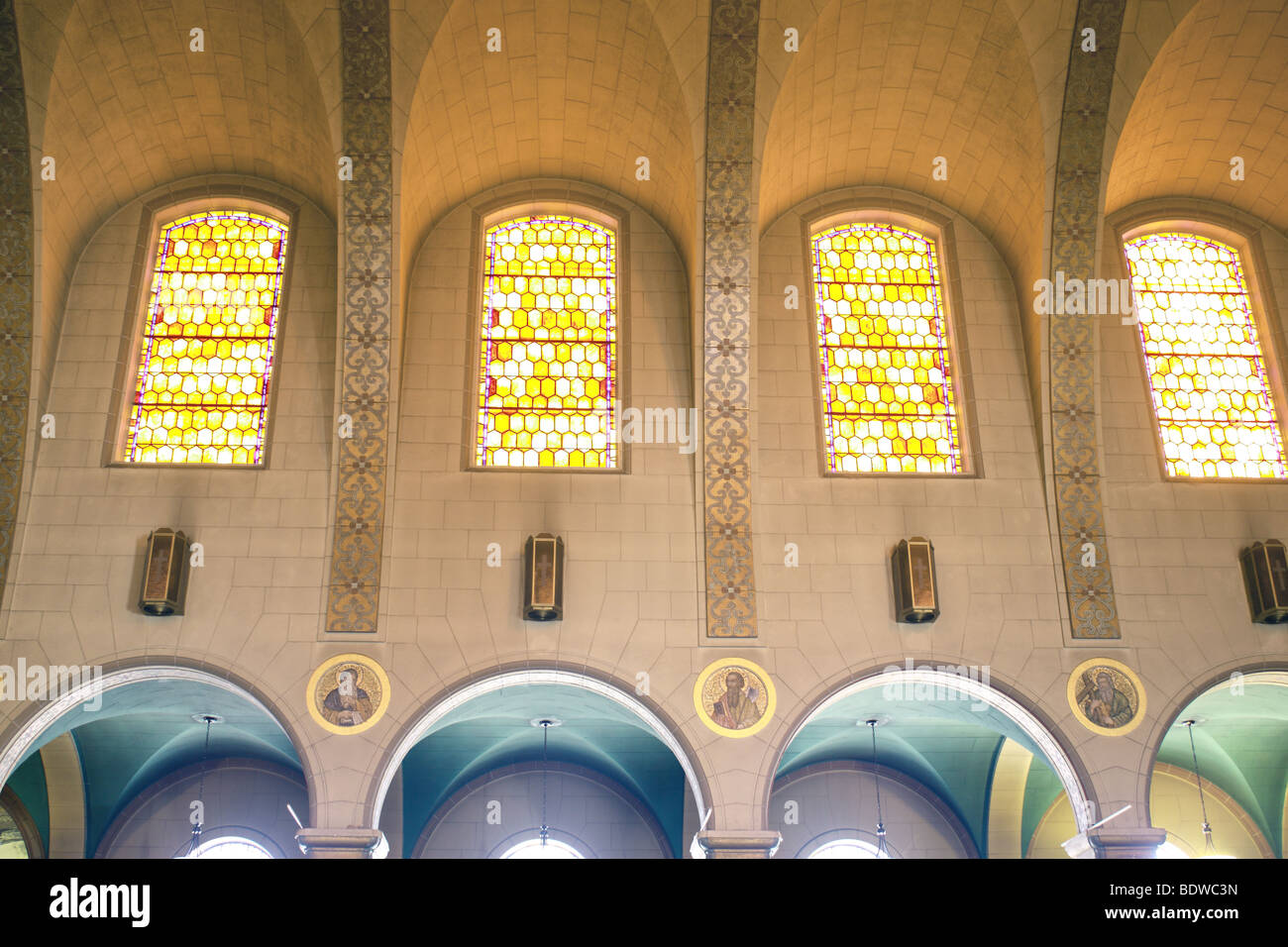 Arcade of colorful glass windows in cathedral - Stock Image