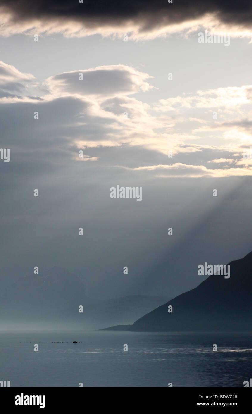 Sun beams illuminate a fishing boat on a fjord in Northern Norway (Styrkesnes, Sörland, Nordland Fylke) - Stock Image