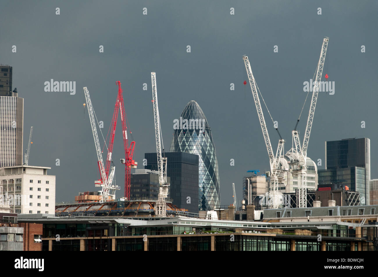 Construction cranes in the City of London on an dark overcast day, London, England, Britain, UK - Stock Image