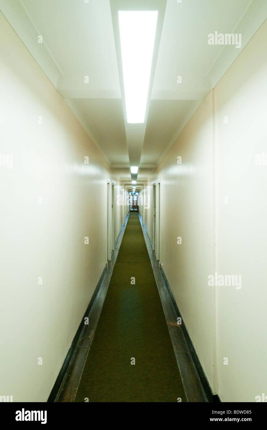Artificial fluorescent lighting in long empty corridor in block of flats, London, England, Britain, UK - Stock Image