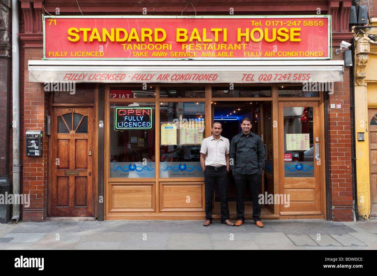 Staff standing outside their Bangladeshi curry and balti restaurant on Brick Lane, Tower Hamlets, London, England, - Stock Image