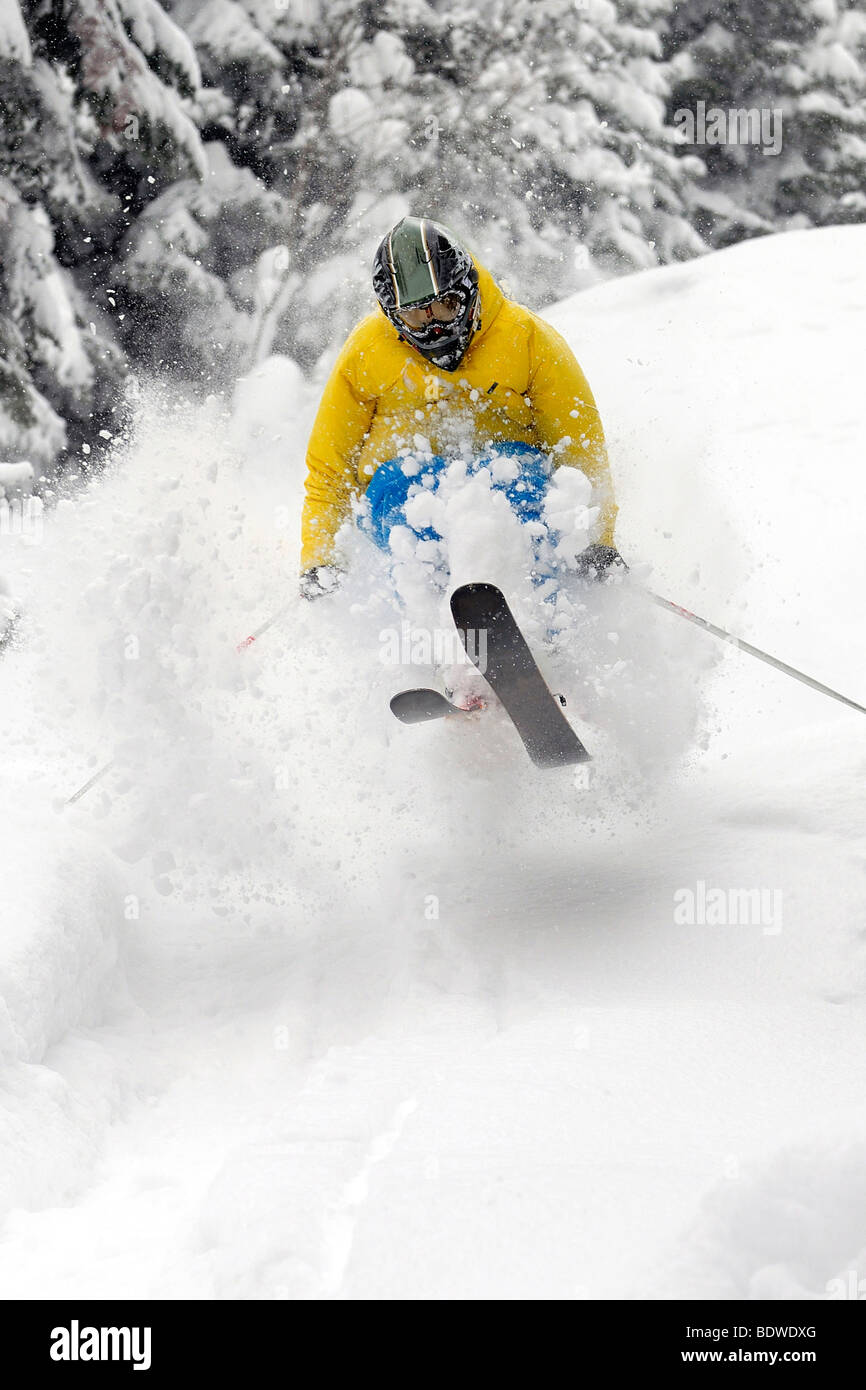 Freeride Skier moving down and jumping in powder snow. - Stock Image