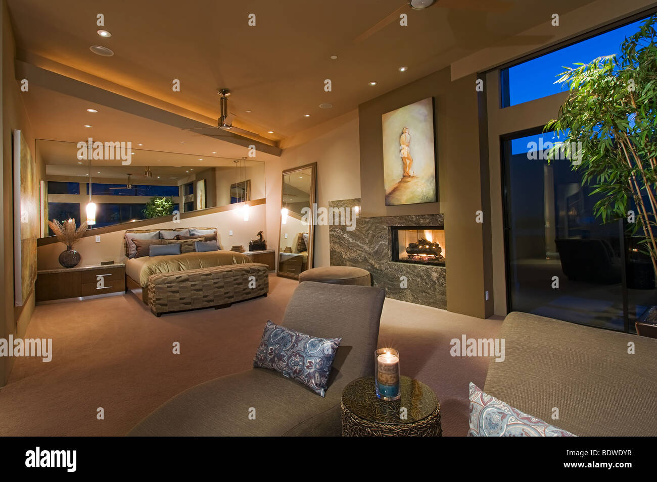 Dramatic modern master suite bedroom shown at night with ...