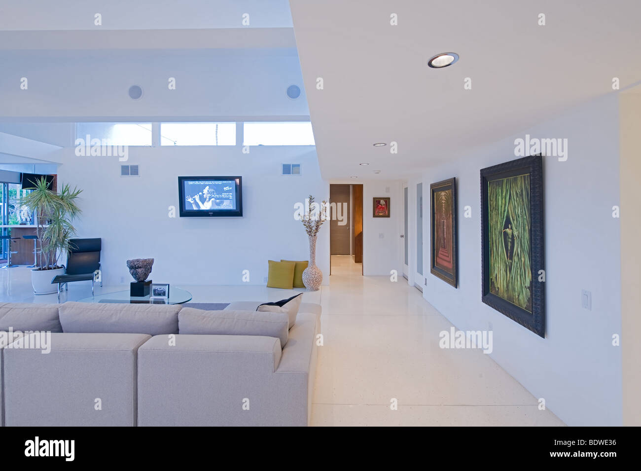 View of art-filled walls of hallway in a restored Palm Springs Mid-Century modern home - Stock Image
